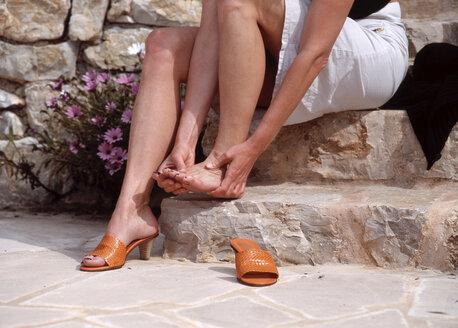 Woman sitting on stairs rubbing feet - PE00131