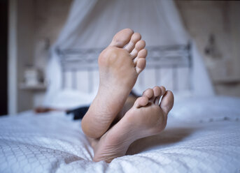 Person lying on bed, close up of feet - 00097PE