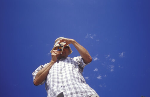 Man taking photograph, low angle view - GS00475