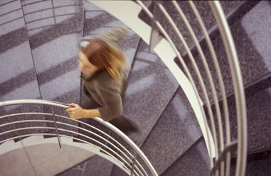 Woman running up stairs - 00196AS