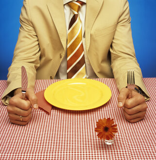 Man sitting at table with empty plate - JLF00020