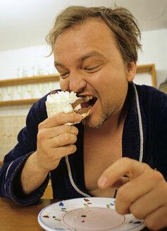 Mature man eating cake slice, close-up - PE00202