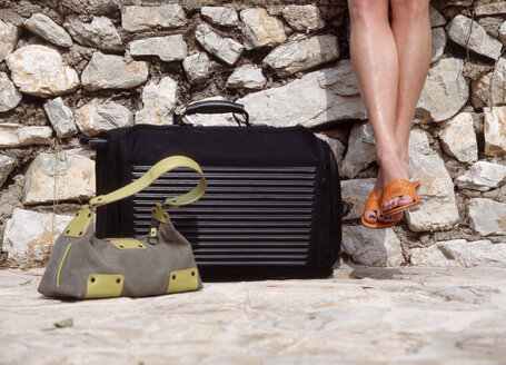 Woman sitting on wall with suitcase and handbag, low section - PE00129