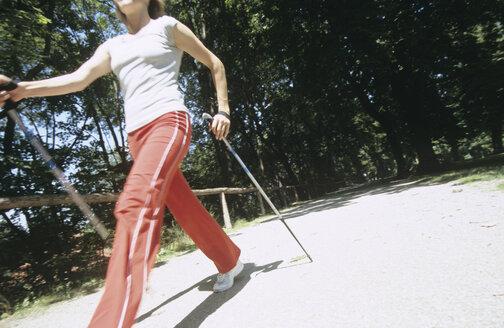 Woman walking with sticks, nordic walking - PEF00363
