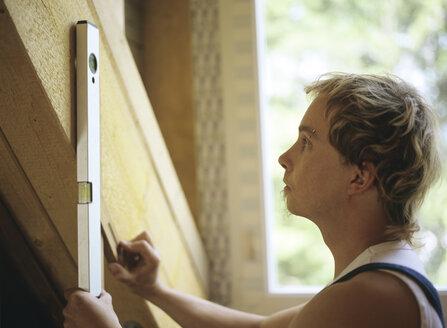 Carpenter using level tool - PEF00344