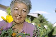 Senior woman in front of flowers, close-up - PEF00327