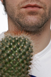 Young man holding cactus plant - LDF00007