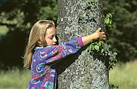 Girl embracing tree, side view - CRF00552