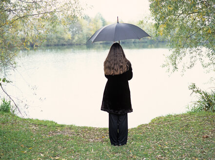 Young woman with umbrella standing at a lake - PE00309