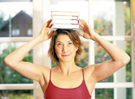 Young woman balancing books on head - PE00297