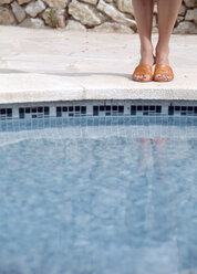 Woman at swimming pool's edge, low-section - PE00134