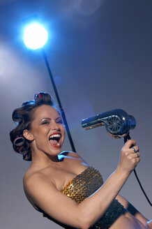 Woman holding hair dryer, singing, portrait - OW00833