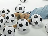 Boy (10-13) lying between football - LMF00059