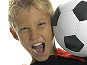 Boy (10-11) with soccer ball on shoulder shouting, close-up - LMF00064