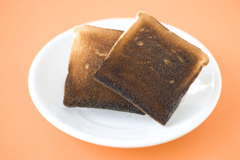 Two slices of burned toast on plate, close-up, elevated view - MNF00093
