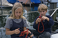 A girl und a boy trying to make a knot - CR00617