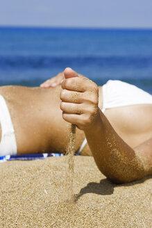 Woman in bikini lying on beach, midsection - LDF00125