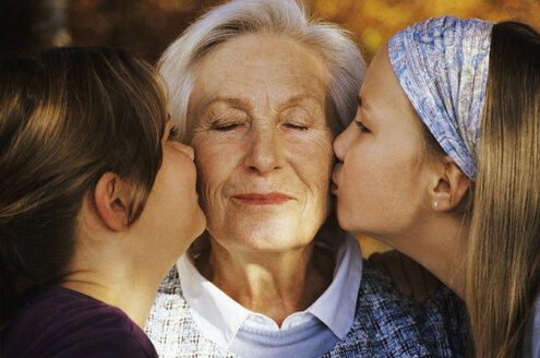 Two girls (8-11) kissing grandmother, close-up - WEPF00017