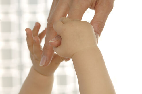 Baby holding mother\\\'s finger - CRF00784