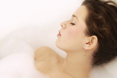 Young woman relaxing in bubble bath, close-up - LRF00019