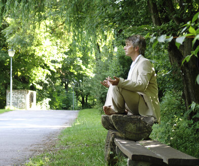 Man sitting on park bench, meditating - DKF00098