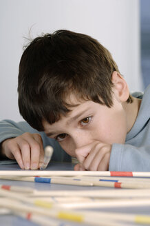 Boy playing with pick-up sticks - CRF00815