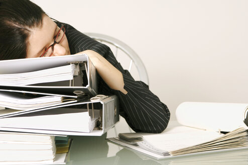 Mid adult woman sleeping at work resting head on pile of files - 00039LRH-U
