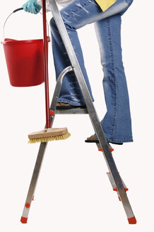 Woman standing on step ladder, holding bucket and brush - 00027LRH-U