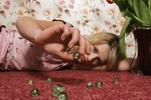 Young woman playing with marbles - CL00068