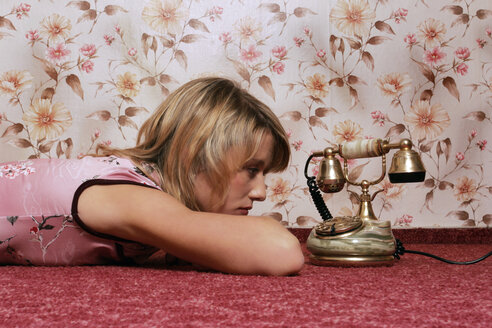 Young woman lying on floor, looking at phone - CL00065