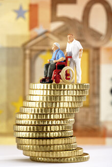 Figurine in wheelchair and caregiver on pile of coins - 03138CS-U