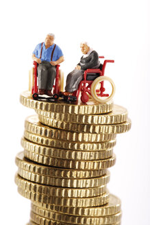 Figurines in wheelchairs on pile of coins - 03129CS-U
