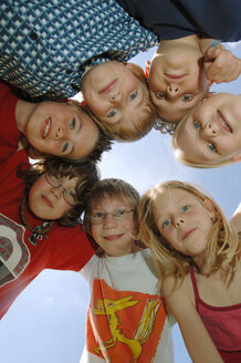 Children (6-9) in huddle, low angle view, portrait - CRF00870