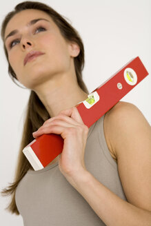 Young woman holding red spirit level looking away, close-up - WESTF00477