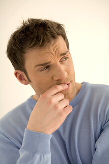 Young man with finger on lips, looking away, close-up - WESTF00450