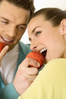 Man and woman eating red apple - WESTF00499
