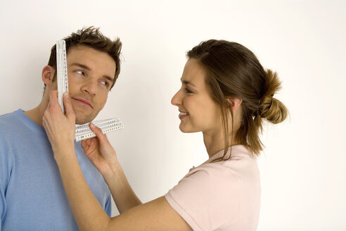 Woman measuring man's face with ruler, smiling, close-up - WESTF00481