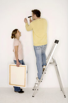 Young couple, man hammering nail into wall - WESTF00586
