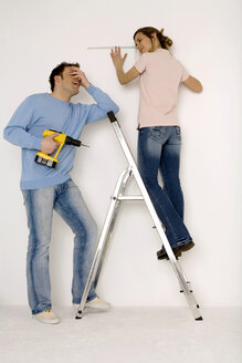 Young couple, man holding electric drill, woman measuring wall with scale - WESTF00573