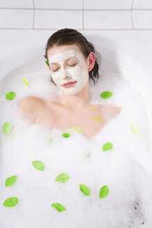 Young woman with face mask taking a bubble bath, eyes closed - MAEF00085