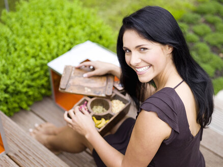 Woman holding spice box, smiling, elevated view - WESTF01024