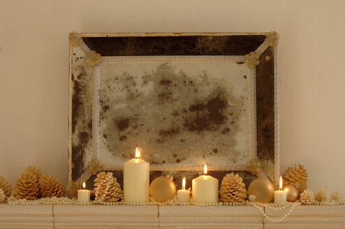 Burning candles with fir cones and frame on shelf , close-up - WESTF01069