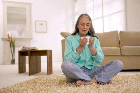 Mature woman holding cup of tea, eyes closed - WESTF00803