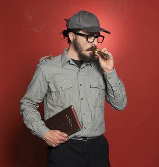 Mature man standing with book, smoking cigar - JL00141