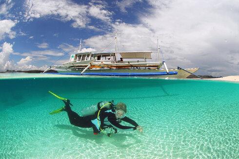 Philippines, Dalmakya Island, woman scuba diver in sea, underwater view - GNF00790