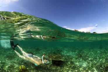 Philippines, Dalmakya Island, woman snorkelling in sea, underwater view - GNF00784
