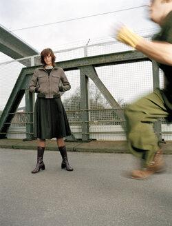 Woman standing on bridge, man running - DB00025