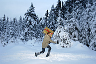 Young man carrying Christmas gift in snow, side view - HHF00456