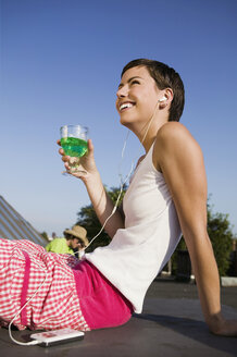 Young woman listening to MP3 player with glass in hand, smiling, side view - WEST01475