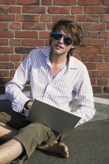 Man using laptop, sitting by wall - WEST01451